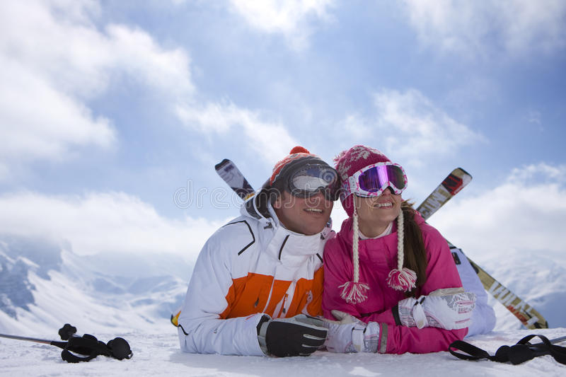 Couple with skis laying in snow on mountain top royalty free stock image