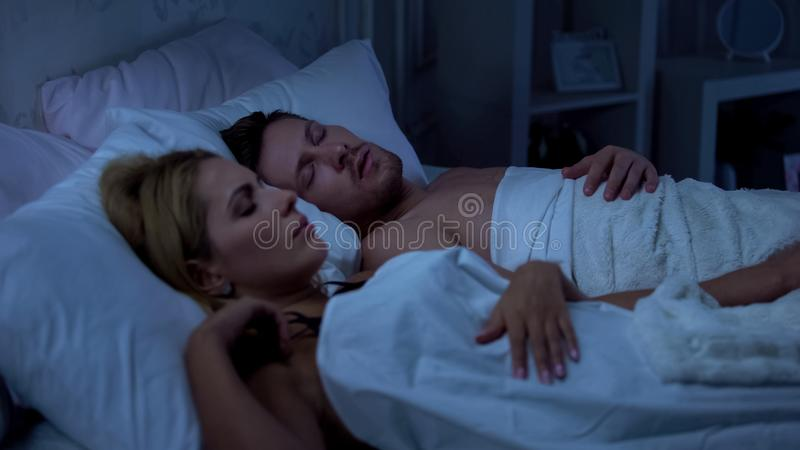 Couple sleeping in bed, husband snoring, health problems, sleeping disorder royalty free stock image