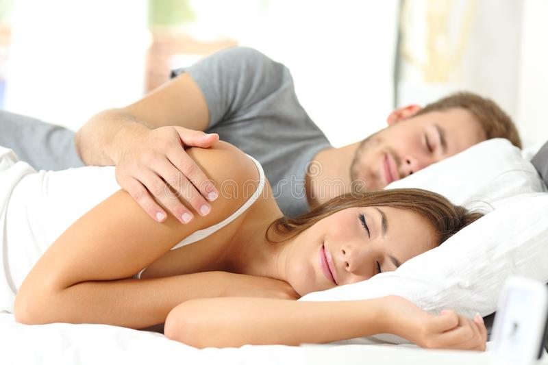 Couple sleeping together in a bed in the morning stock image