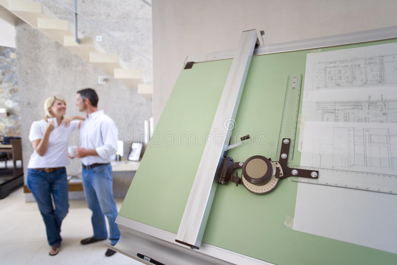 Couple smiling at each other indoors, blue prints on drafting board in foreground royalty free stock image