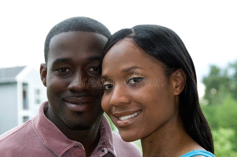 Couple in Smiling Embrace - Horizontal. Attractive young couple, with toothy similes, looking at the camera, in a close-up embrace. Horizontally framed portrait royalty free stock photo