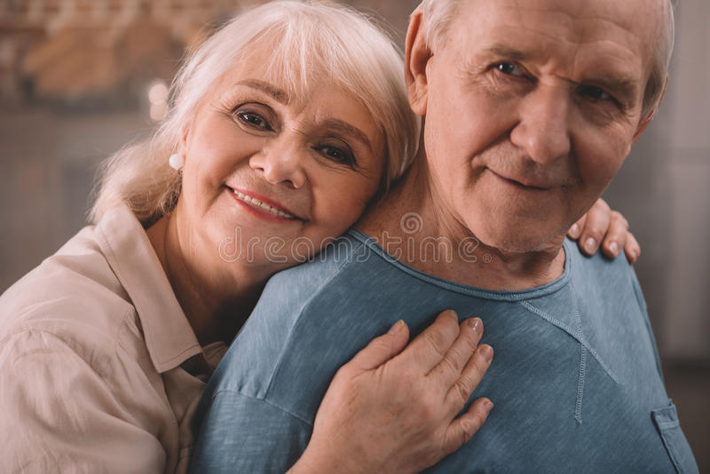 Couple smiling and hugging at home. Senior couple smiling and hugging at home royalty free stock image