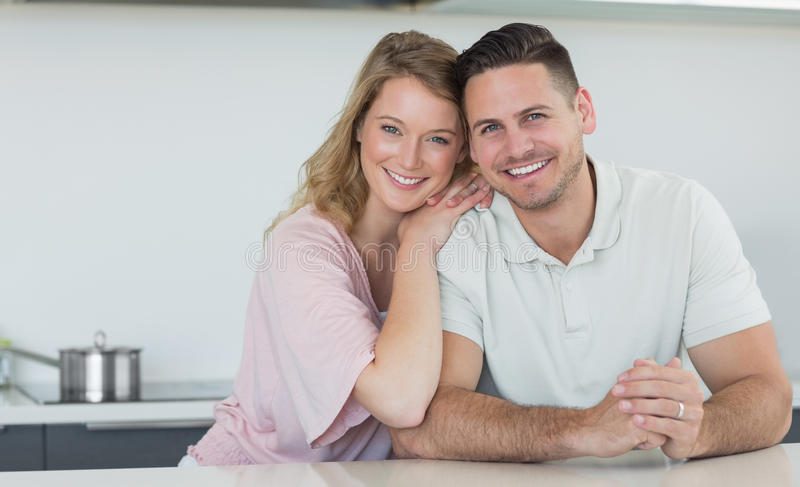 Couple smiling at kitchen counter royalty free stock photos