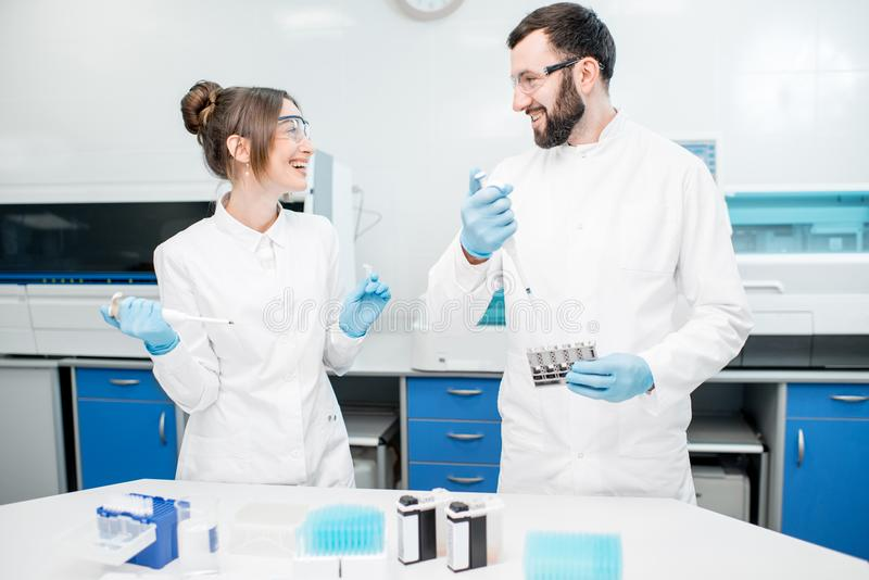 Laboratory assistants working with test tubes. Couple of smiling laboratory assistants in uniform working with analysis in test tubes at the medical laboratory royalty free stock photo