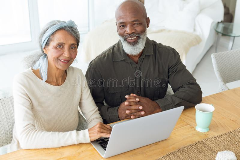 Couple smiling while using white laptop on table and the man holds a cup stock photography