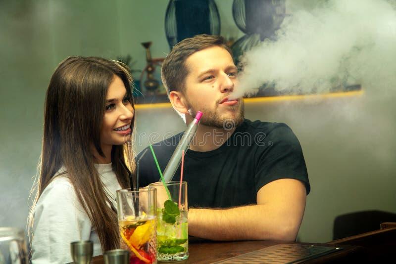 Couple smokes shisha at the bar stock image