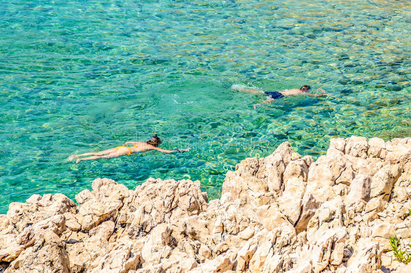 A Couple Snorkeling In The Crystal Clear Rocky Adriatic