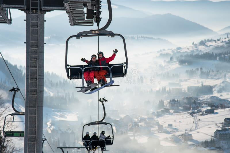 Couple snowboarders having fun on a ski lift in ski resort with beautiful background of snow-covered slopes, hills royalty free stock image
