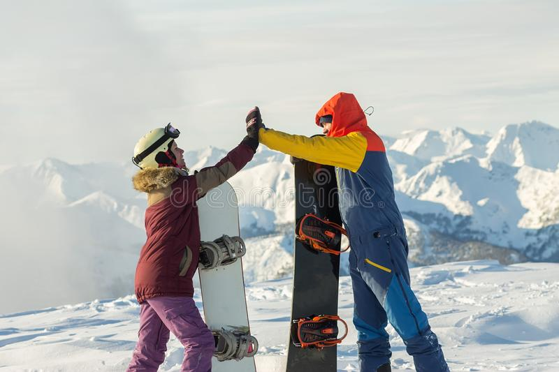 Couple snowboarding freeriders man and a woman give five with snowboards. Couple snowboarding freeriders men and a women give five with snowboards stock photography