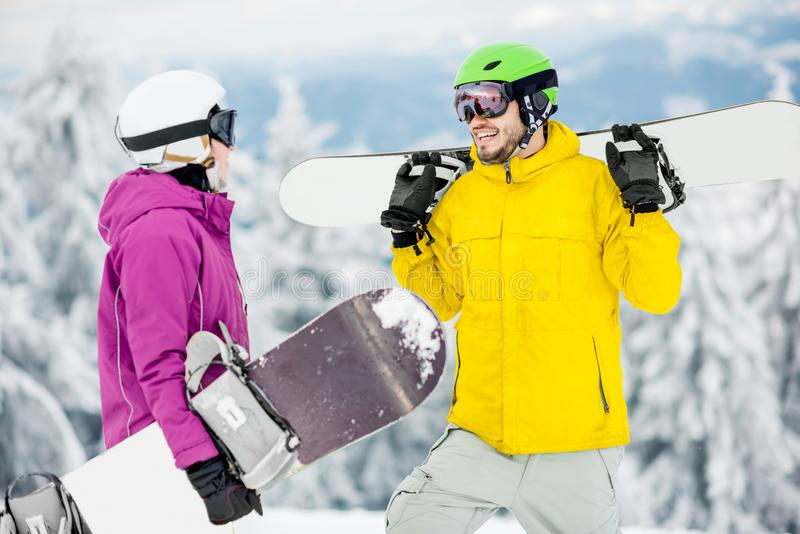 Couple with snowboards on the snowy mountains stock photos