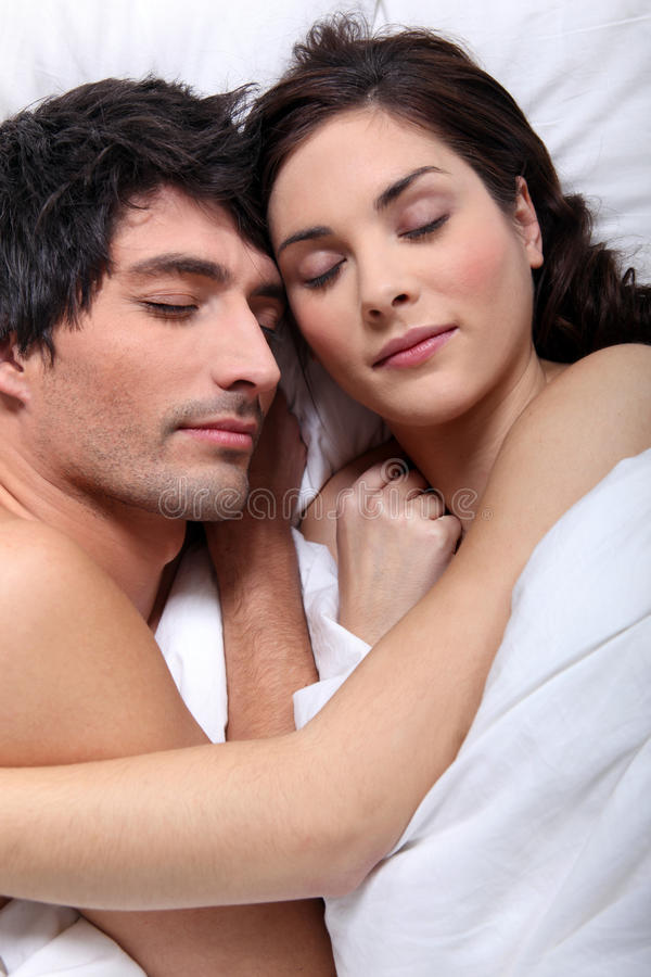 Couple snuggling in bed. Together royalty free stock image