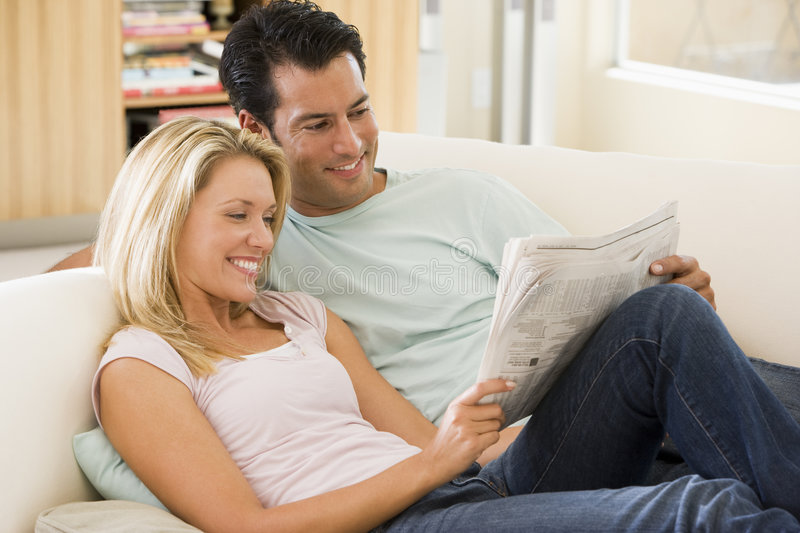 Couple on sofa at home. Couple relaxing on sofa reading newspaper at home