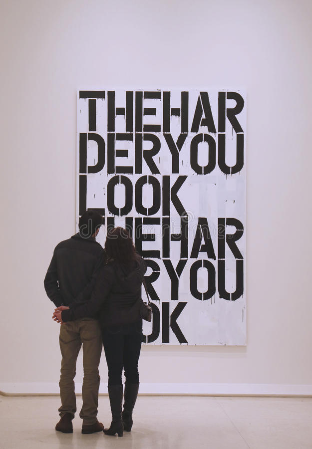 Couple in Solomon R Guggenheim Museum of modern and contemporary art in New York during Christopher Wool exhibition royalty free stock images