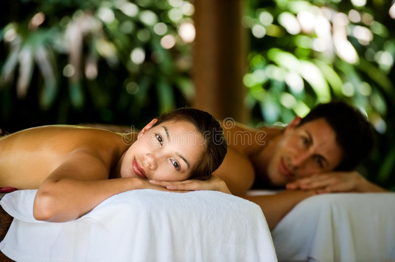 Couple At Spa. An attractive young couple lying on massage beds at a spa outdoors