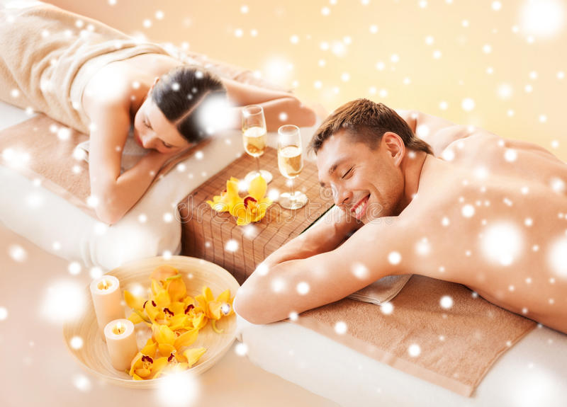Couple in spa. Health and beauty, honeymoon and vacation concept - couple in spa salon lying on the massage desks stock images