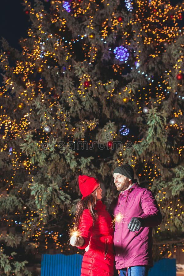 Couple with sparklers in front of large Christmas tree royalty free stock image