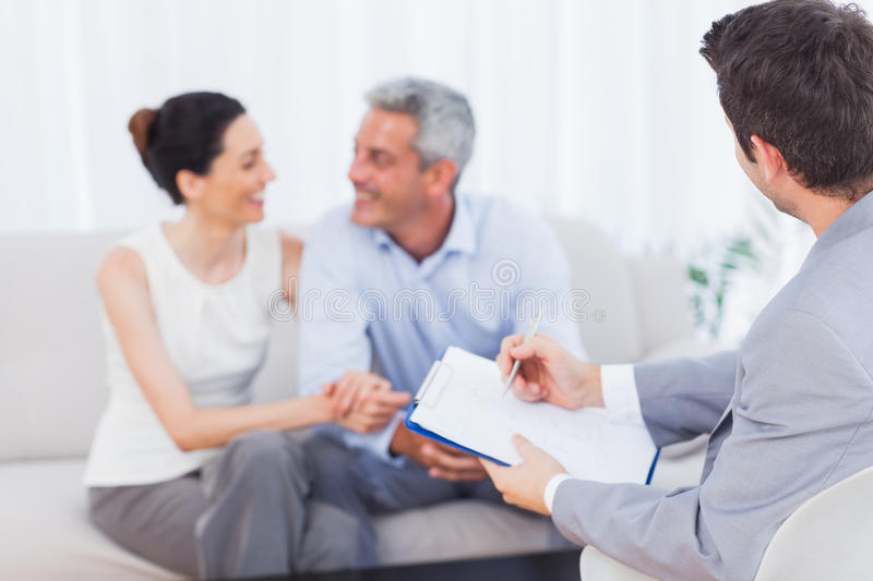 Couple speaking while salesman is holding contract royalty free stock photos
