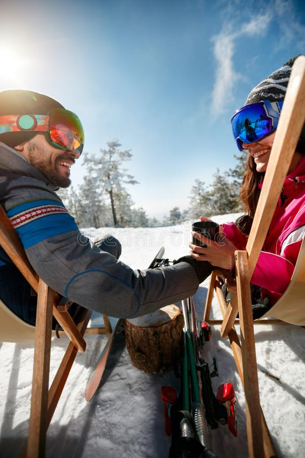 Couple spending time together and drink after skiing in ski resort. Back view royalty free stock images
