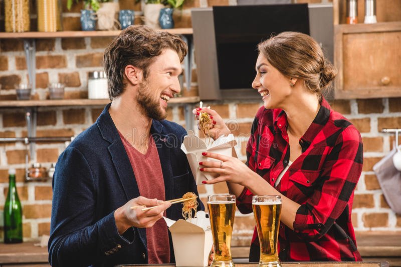 Couple spending time together. Happy couple spending time together, eating noodles, women feeding man stock images