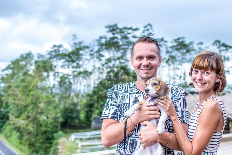 Couple spending time together with puppy beagle dog on a tropical background of Bali island, Indonesia. royalty free stock image