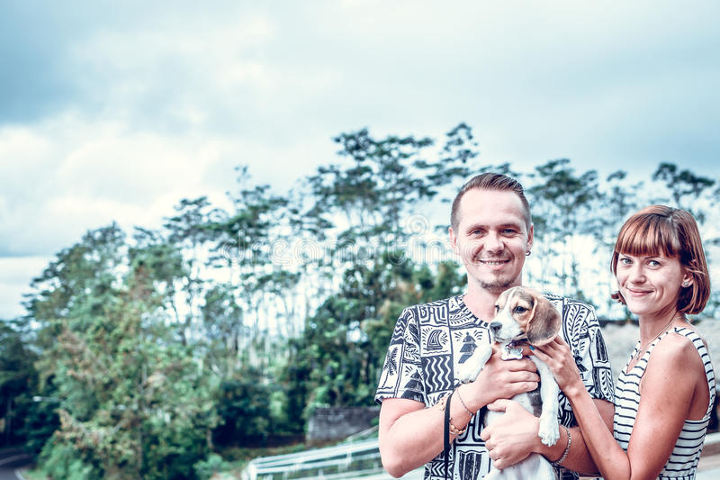 Couple spending time together with puppy beagle dog on a tropical background of Bali island, Indonesia. stock photo