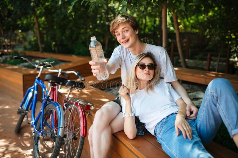 Couple spending time on wood bench in park with two bicycles near. Young man sitting on bench and happily looking in royalty free stock photography