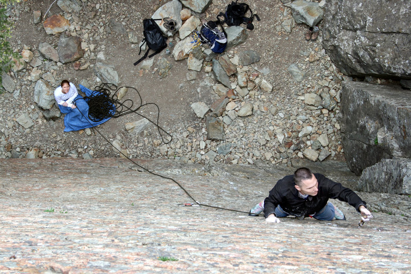 Couple sport rock climbing. A man rock climbing sport (clipping bolts) on lead view from above stock photos