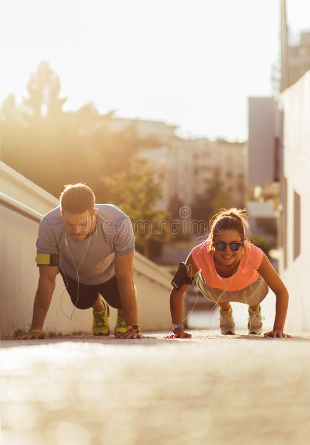 Fitness and healthy couple training while doing push-ups. Couple in sportswear doing push-ups on the ground on urban place stock image