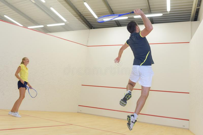 Couple with squash rackets indoor training club. Couple stock images