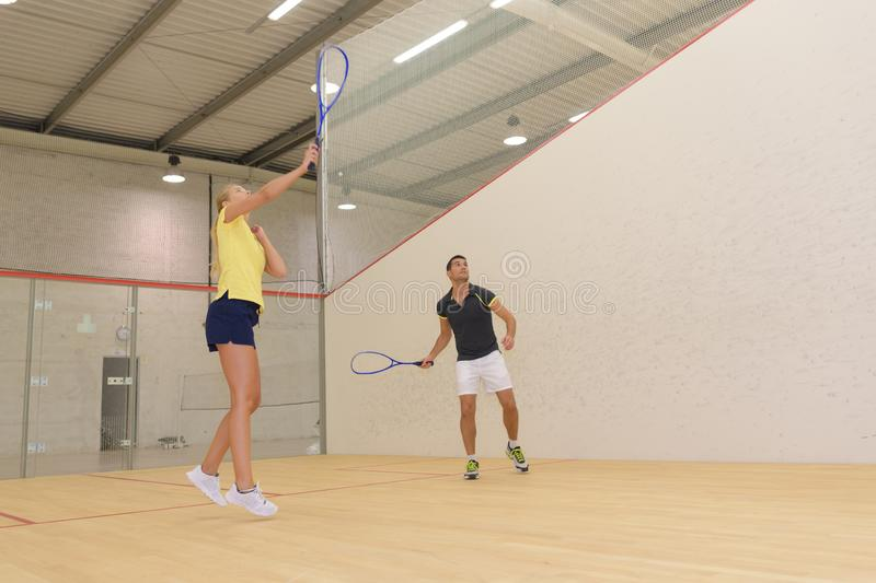 Couple with squash rackets playing indoor stock photography