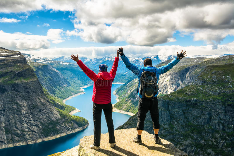 Couple standing against amazing nature view on the way to Trolltunga. Location: Scandinavian Mountains, Norway, Stavanger. Artist royalty free stock photo