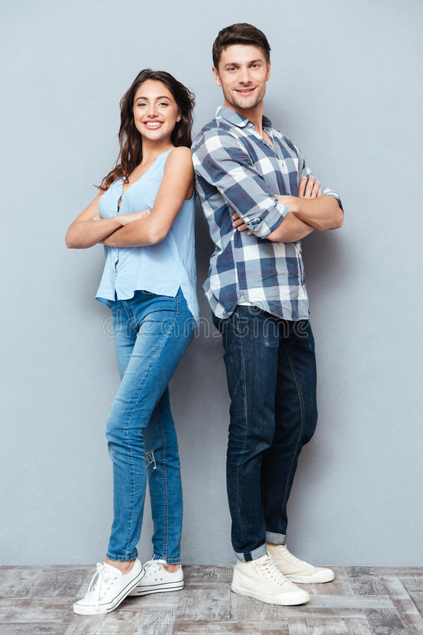 Couple standing with arms crossed over gray background royalty free stock photography