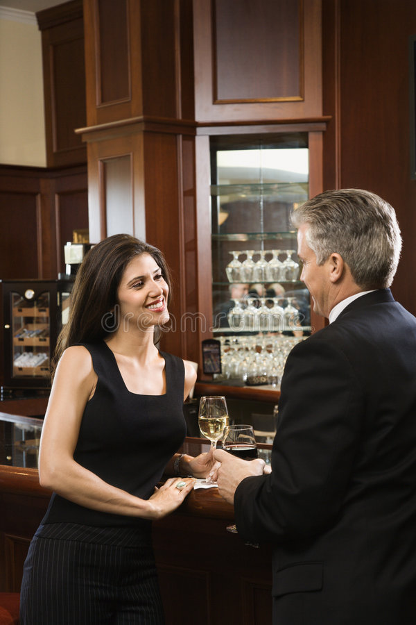 Couple standing at bar. stock photos