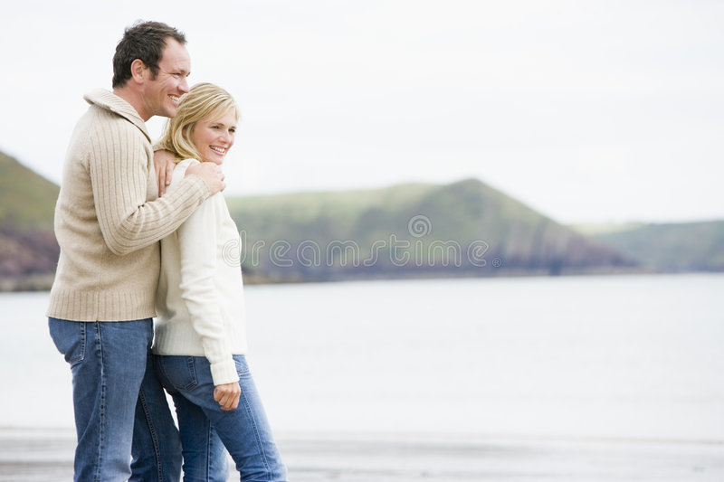 Couple standing on beach smiling royalty free stock photos