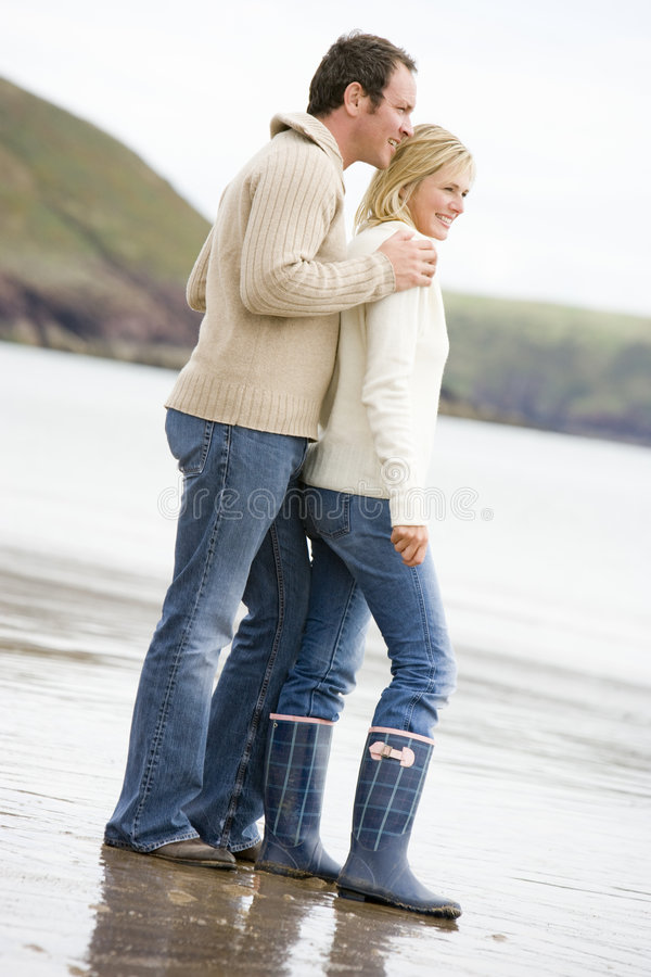 Couple standing on beach smiling stock images