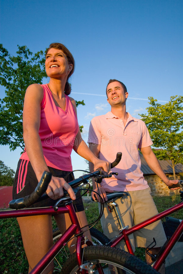 Couple Standing by Bikes - Vertical. Couple standing by their bikes looking off into the distance smiling. Vertically framed photograph stock photos