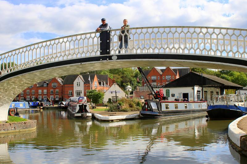 Couple standing on bridge by canal marina. Couple standing on foot bridge at the entrance to Braunston marina on the Grand Union Canal in England royalty free stock image