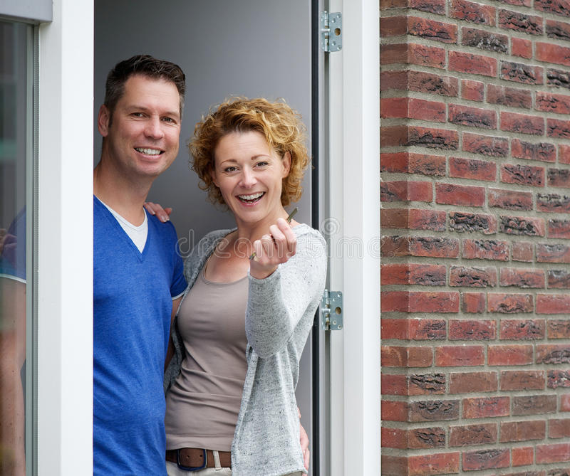 Couple standing by door of new home holding keys. Portrait of a cheerful couple standing by door of new home holding keys stock images