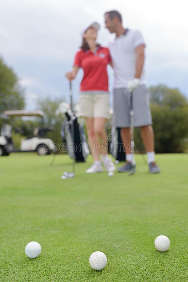 Couple standing on golf course stock image