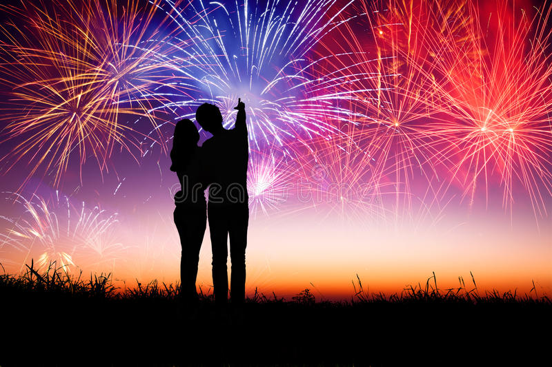 Couple standing on the hill and watching the fireworks stock images