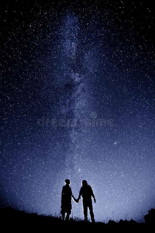 Couple is standing in mountains against night sky with milky way stock photos
