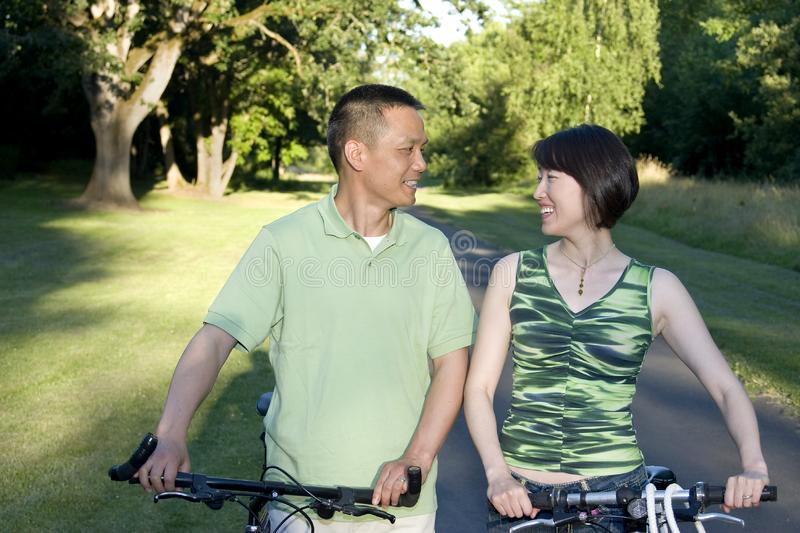 Couple ] Standing Next to Bicycles - Horizontal royalty free stock photography