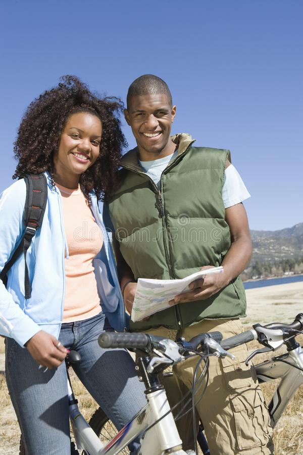Couple Standing With Roadmap And Mountain Bikes. Portrait of an happy African American couple standing with roadmap and mountain bikes stock images
