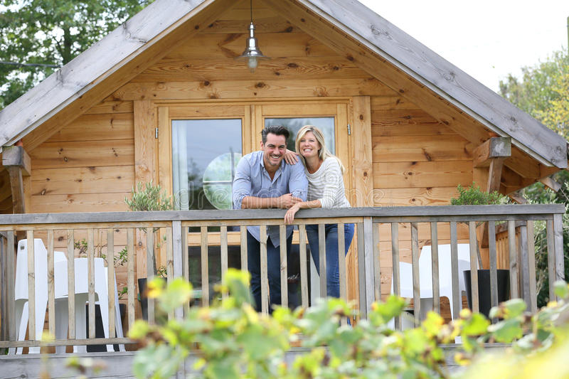 Couple standing on terrace of wooden cabin. Couple standing in log cabin terrace stock images