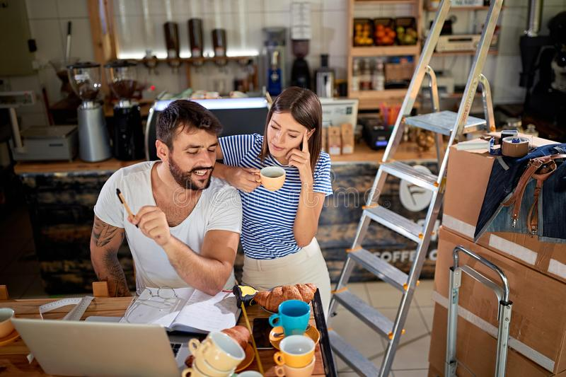 Couple standing in their new coffee shop and working to open. Young couple standing in their new coffee shop and working to open royalty free stock photography