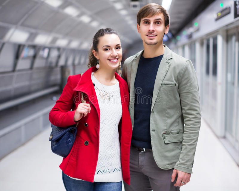 Couple standing at underground platform stock photos