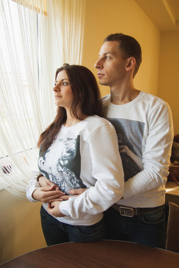 Couple standing by window royalty free stock image