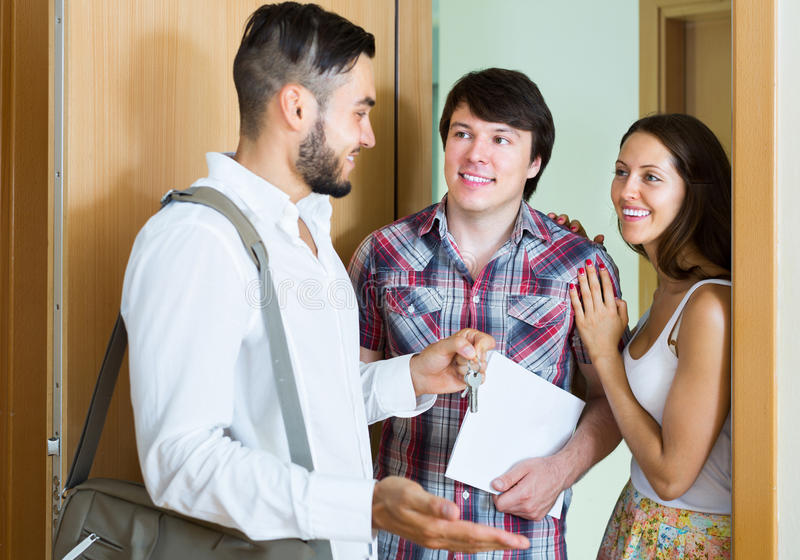Couple stands with realtor in the doorway royalty free stock photos