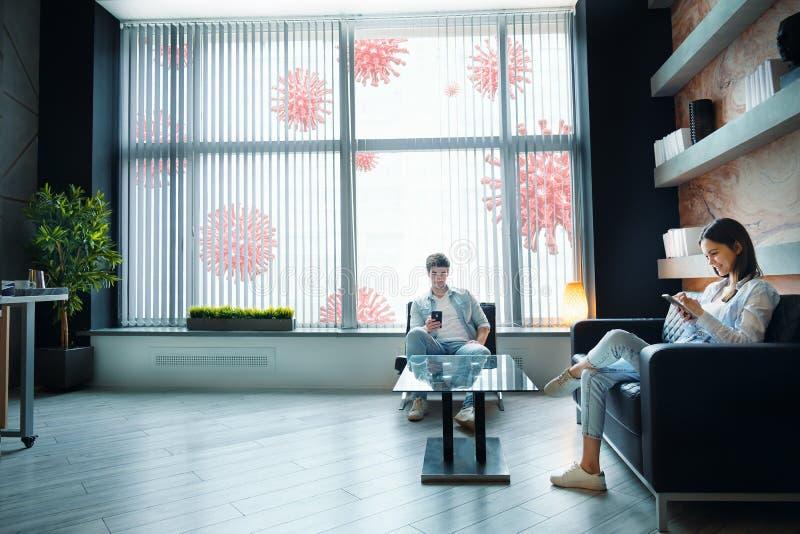 Couple staying at home, using phones, coronavirus outside. Self-quarantine coronavirus isolation concept. Couple staying at home, using phones, siting on sofa at stock image