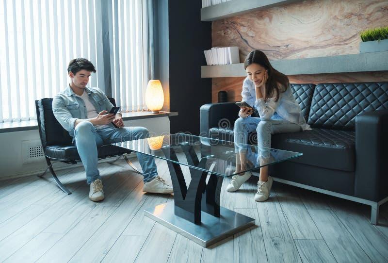 Couple staying at home, using phones, siting on sofa at home, using social media, ignoring coronavirus outside. Self. Quarantine coronavirus isolation concept royalty free stock photos